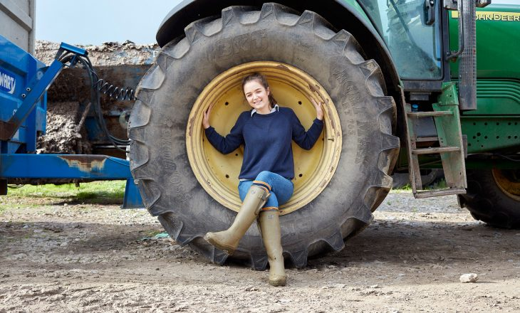 A young girl rests against a tractor tire.